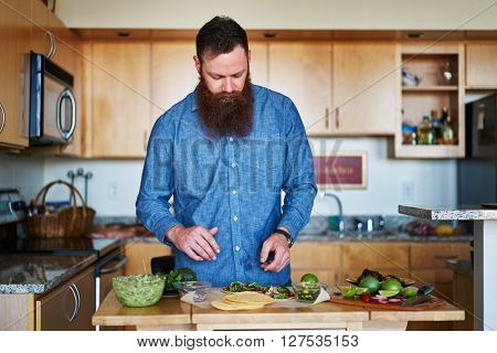 man making tacos at home in the kitchen