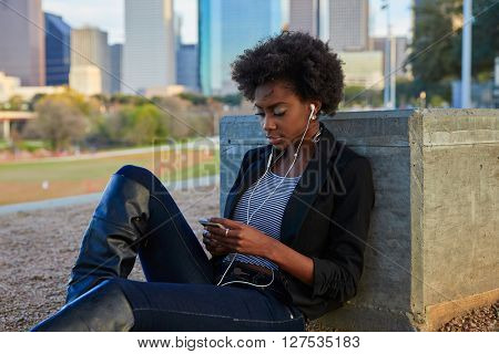 Woman with smartphone sitting in the park listening music dress in black