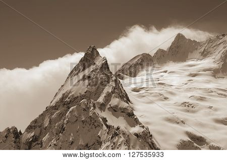 Sepia snowy mountains. Caucasus Mountains region Dombay. Peak Ine.