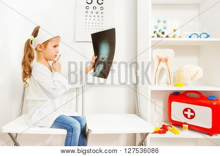 Cute young doctor in whites and cap holding a skull x-ray at the medical room