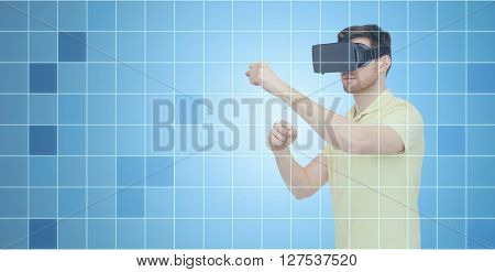 3d technology, virtual reality, entertainment and people concept - young man with virtual reality headset or 3d glasses playing game and fighting over blue grid background
