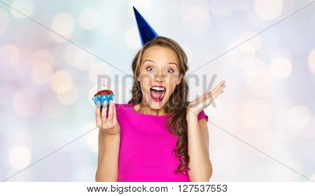 people, holidays, emotion, expression and celebration concept - happy young woman or teen girl in pink dress and party cap with birthday cupcake over holidays lights background