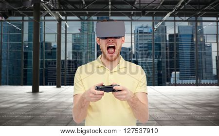 3d technology, virtual reality, entertainment and people concept - young man with virtual reality headset playing with game controller gamepad over empty industrial room and city panorama background