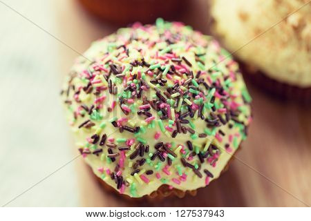 food, junk-food, culinary, baking and eating concept - close up of glazed cupcake or muffin on table