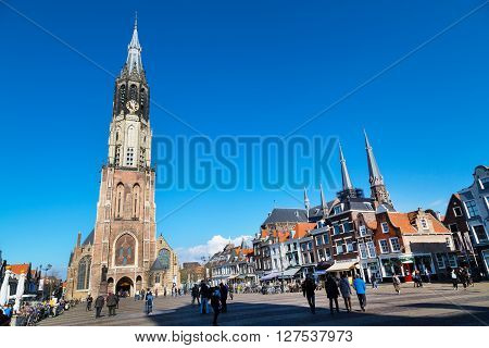 Delft, Netherlands - April 8, 2016: Colorful street view with traditional dutch houses on the square, Nieuwe Kerk or New Church, people walking in downtown of popular Holland destination