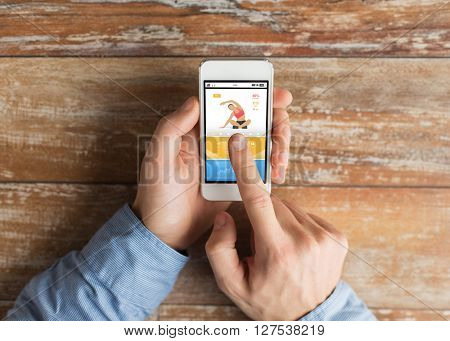 sport, fitness, people and technology concept - close up of male hands holding smartphone and pointing finger to sports application on screen
