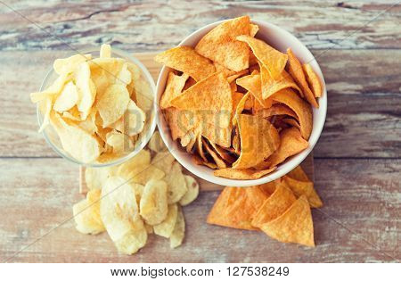 fast food, junk-food, cuisine and eating concept - close up of potato crisps and corn nachos in bowls on table