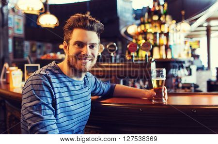 people, drinks, alcohol and leisure concept - happy young man drinking beer at bar or pub