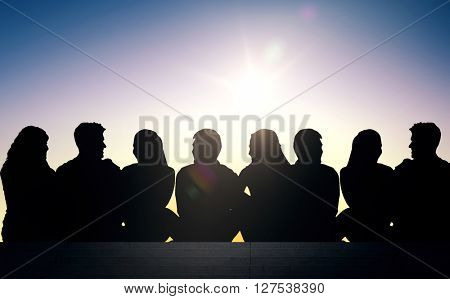 friendship, leisure, summer and people concept - silhouettes of friends sitting on stairs over sun light background