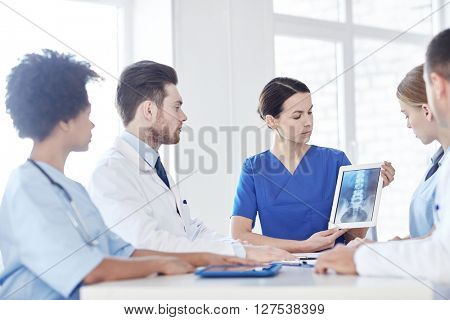 profession, people, surgery, radiology and medicine concept - group of doctors with x-ray on tablet pc computer screen meeting at medical office
