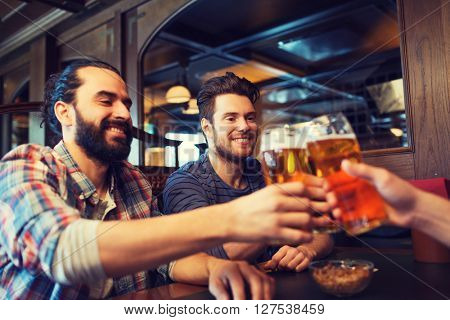 people, leisure, friendship, bachelor party and celebration concept - happy male friends drinking beer and clinking glasses at bar or pub