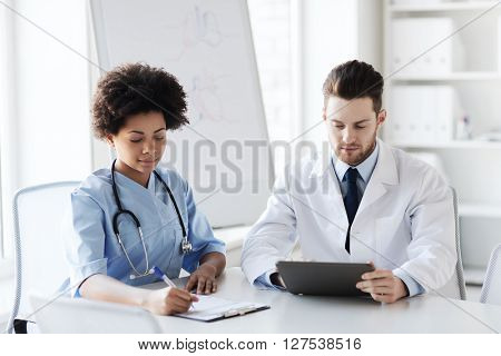 hospital, profession, people and medicine concept - two doctors with tablet pc computer meeting and talking at medical office