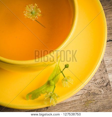 Yellow cup with linden tea on the table top view