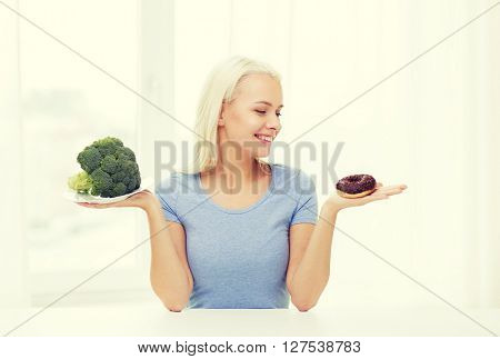 healthy eating, junk food, diet and choice people concept - smiling woman choosing between broccoli and donut at home