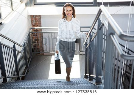 Portrait of businesswoman holding a briefcase and climbing staircase in office