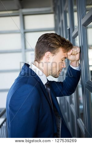 Tired businessman leaning on door in office