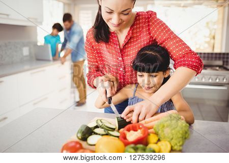 Close-up of happy mother teaching daughter to cut vegetables at home