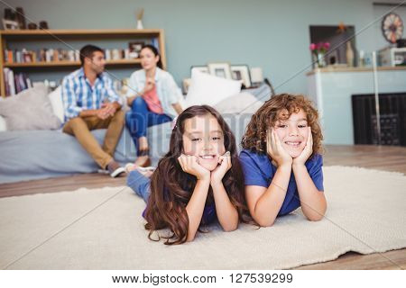 Portrait of children lying on carpet while parents sitting in background at home