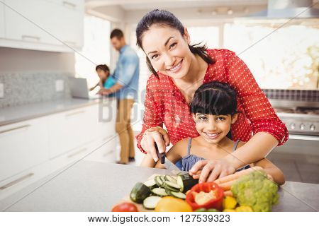 Close-up of portrait of happy mother teaching daughter to cut vegetables at home