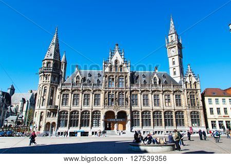 Ghent, Belgium - April 12, 2016: Old Post Office building with the clock tower against blue sky, people at the square in Ghent, Belgium