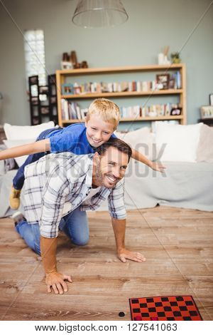 Happy father and son playing on hardwood floor at home