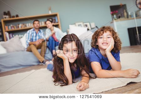 Portrait of children resting on carpet while parents sitting in background at home