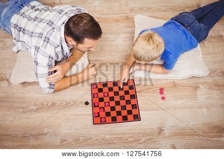High angle view of father and son playing checker game while lying on floor at home