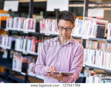 Happy male student holding books at the library