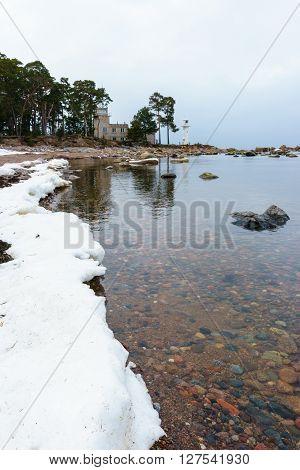 Baltic sea coast by winter and Vergi lighthouse afar