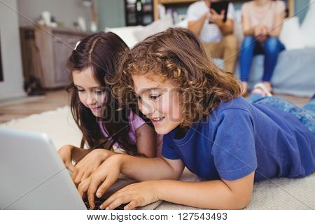 Close-up of siblings using laptop while lying on carpet at home