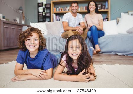 Close-up of cheerful son and daughter lying on carpet while parents sitting on sofa at home