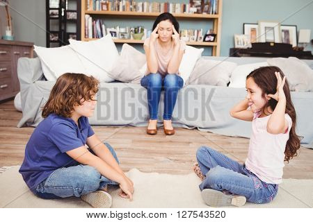 Close-up of children playing while tensed mother sitting on sofa at home