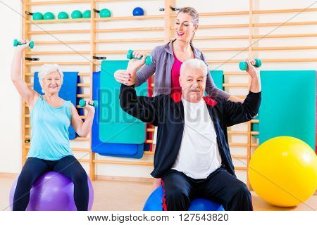Physiotherapist coaching senior people exercising with dumbbells