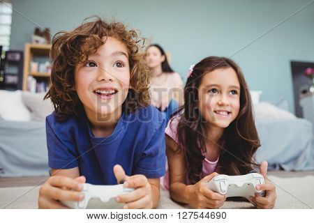 Close-up of happy siblings with controllers playing video game on carpet at home