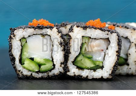 Set of delicious sushi rolls with white fish and cucumber in black and orange tobiko roe on blue background closeup