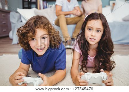 Close-up siblings with remote playing video games on carpet at home