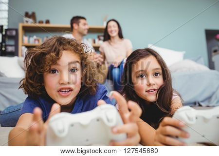 Close-up of cheerful siblings with controllers playing video game on carpet at home