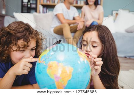 Close-up of children pointing at globe while parents in background at home