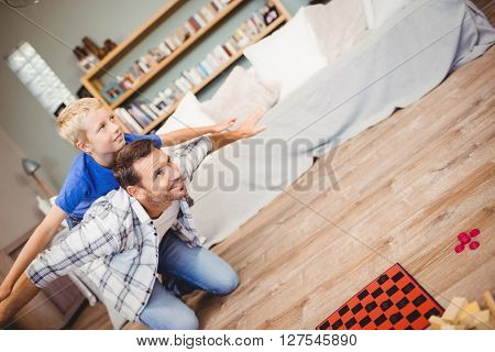 Tilt image of father and son playing on hardwood floor at home