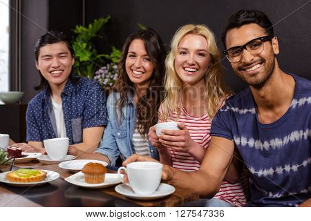 Smiling friends enjoying coffee together and using technologies at the coffee shop