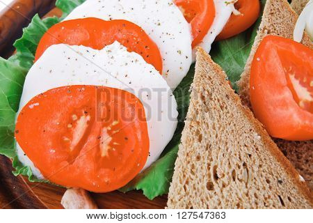 light feta slices on wooden plate with tomatoes