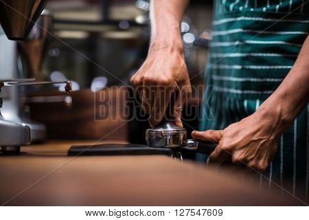 Waiter squeezing the coffee in the percolator at the coffee shop