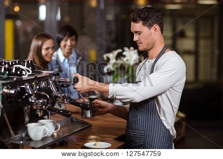 Barista making hot milk with coffee machine in the bar
