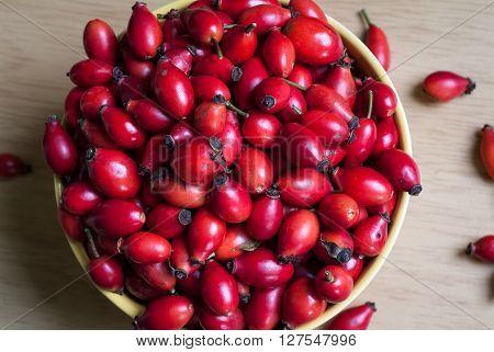 closeup photo of a yellow bowl full of rosehip berries