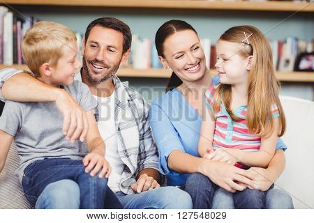 Close-up of happy family sitting on sofa at home