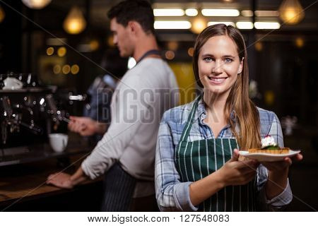 Pretty barista holding dessert and smiling at the camera in the bar