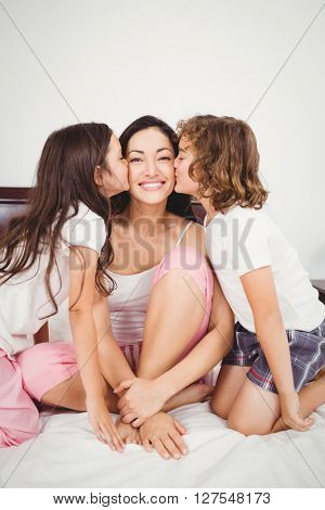 Close-up of son and daughter kissing happy mother on bed at home