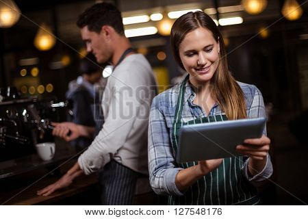 Pretty barista using tablet in the bar