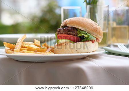 Hamburger and fries at restaurant outdoor table