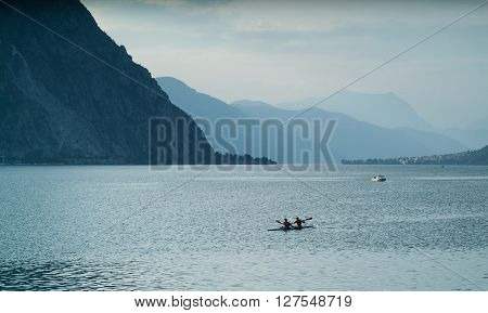 Lecco, Italy - September 1st 2015: Two canoe rowers photographjed at Lake Como near Lecco Italy on September 1st 2015.
